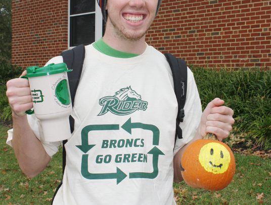 Junior Sean Lonesky shows off his Broncs Go Green mug and painted pumpkin from the Sustainability Day festivities on Oct. 21. The annual event aims to promote earth-friendly practices.