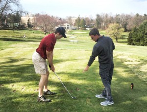 Golf  Head Coach Jason Barry, right, instructs junior Luke Liddell during a rare outdoor practice.