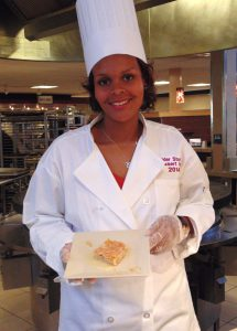 Junior advertising major Leonora Paul prepares her winning Lemongrass Glazed Apple Cake for hungry students.