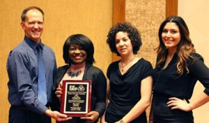From left, Dr. Ron Cook, Kai Wright, Caroline Romanelli and Kristin Lopez, hold their first-place award from the Small Business Institute Consulting Project of the Year Competition.