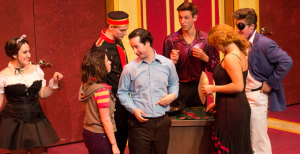 From left, Chrissy Hartzell, Chloe Voreis, Braden Sweeney, Eric Dann, Chris Hansell, Abbey Sierakowski, and Travis Przybylski come together as the cast for Rider Theater's rendition of Lucky Stiff, a musical that follows Harry Witherspoon, portrayed by Dann, as he is thrown on an unexpected trip to Monte Carlo to take his dead uncle on one final vacation to be able to inherit a $6 million fortune.