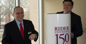 Mordechai Rozanski  and student Nick Lim fill the time capsule on April 27. Lim is a member of the sesquicentennial committee, which initiated  the time capsule and collected items from recent years.