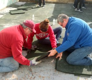 Dean of Students Anthony Campbell, senior Hannah Bass and Joe Saphire, president of the Millhill board of directors, help resurface the playground at Millhill Child  & Family Development.