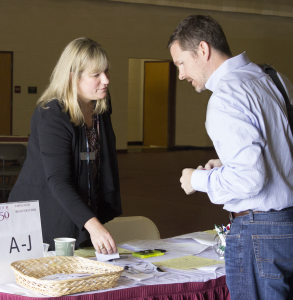 The executive director of Career Services, Kim Barberich, signs in Johnson & Johnson employer Brad Updegrove at the career fair.