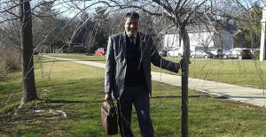 Iraqi professor Dr. Abdulhussein Kadhim Reishahn stands next to a tree planted in honor of the relationship between Rider and Kufa in the Second Global Village.