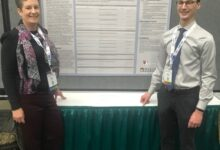 Photo of Associate professor and graduate student present research at psychologist convention